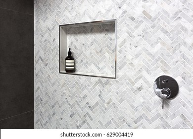 Shower shelf detail in wall of herringbone marble tiles