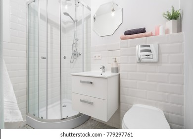 Shower, sink and toilet in white bathroom with metro tiles
