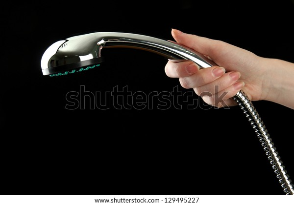 Shower in woman hand on black background
