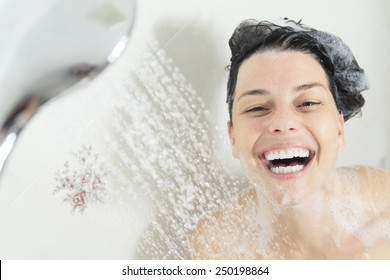 Shower woman. Happy smiling woman washing shoulder showering in bathroom.