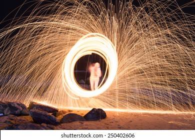 Showers of hot glowing sparks from spinning steel wool at Coney Island Beach, Brooklyn, New York.