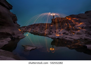 Showers of hot glowing sparks from spinning steel wool on the rock at Sam pan boke (3000 boke) Ubonratchatani, Thailand. The panoramic nature of rock in Mae Khong River, Thailand and Lao border.