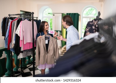 Showing a blazer to husband. Radiant charming alluring nice-looking stylish dark-haired lady showing a blazer with a sale tag on it to her bearded attractive cheerful man in the showroom.