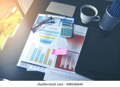 Showing business and financial report. Accounting with Business stuff, Graph, charts, calculator, glasses , pen and a cup of coffee.