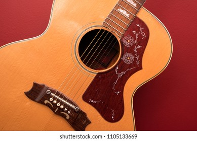 Showing close up of 6 string guitar body, guitar is orange and accented, background is red.