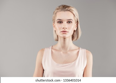 Showing flawless skin. Appealing young lady with bob haircut and grey eyes looking natural during photo shoot