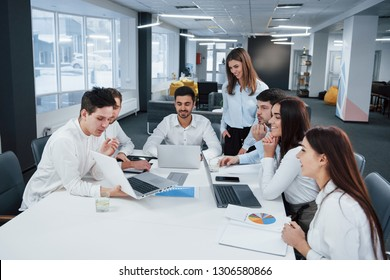 Showing good results. Group of young freelancers in the office have conversation and smiling. - Shutterstock ID 1306580866