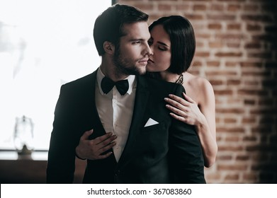 Showing her love. Close-up beautiful young woman standing behind her boyfriend wearing suit and giving him a kiss in cheek