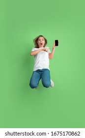 Showing phone screen in jump. Caucasian young woman's portrait isolated on green studio background. Beautiful female model in white shirt. Concept of human emotions, facial expression, sales, ad