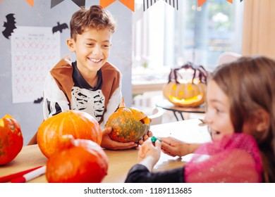 Showing pumpkin. Happy beaming boy wearing skeleton costume showing little pumpkin his beautiful dark-haired friend