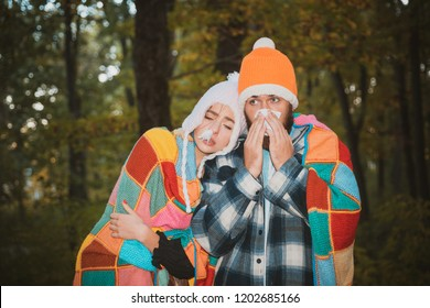 Showing sick couple sneezing at autumn park. Girl with handkerchief and sneezing boy in autumn park. Sick couple catch cold. Sick couple are trying to sneeze in the napkin. Stop the flu epidemy