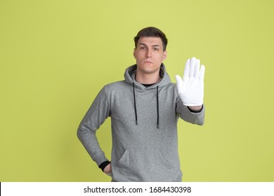 Showing stop sign. Caucasian man's portrait isolated on yellow studio background. Freaky male model using gloves. Concept of human emotions, facial expression, sales, ad. Unusual appearance.