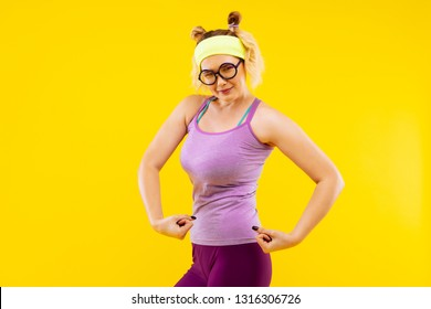 Showing strength. Young funny woman wearing purple leggings and camisole showing strength