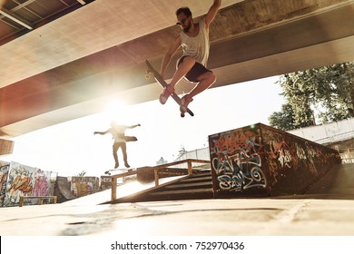 Showing their best tricks. Two young men skateboarding at the skate park together