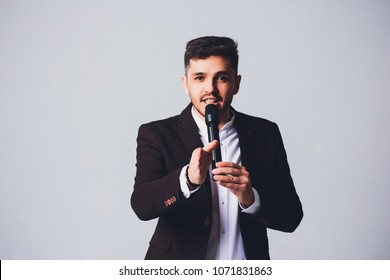 Showman interviewer with emotions. Young elegant man holding microphone against white background.Showman concept.