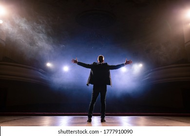 Showman. Middle Age Male entertainer, presenter or actor on stage. Arms to sides, smoke on background of spotlight. Rear view portrait of a male public speaker speaking at the microphone, pointing