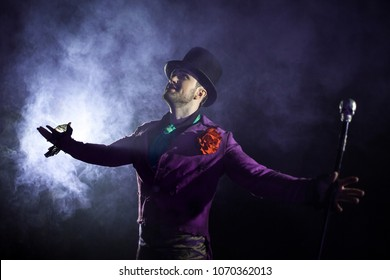 Showman presents his show, spreading his hands to the sides. The guy in the purple camisole and the cylinder. Bright tailcoat, suit