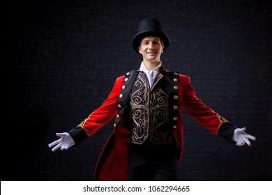 Showman. Young male entertainer, presenter or actor on stage. The guy in the red camisole and the cylinder spreading hands