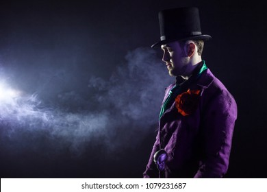 Showman. Young male entertainer, presenter or actor on stage. The guy in the purple camisole and the cylinder. Bright tailcoat, suit