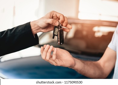 Showroom Dealer The Gives Car Keys To The Buyer. Dialogue With A Dealer. Cheerful Customer. Automobile Salon. Make A Decision. End Of A Deal. Good Offer. New Buying. Business Trade.