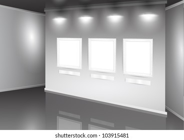 showroom with empty wall with three frames and light