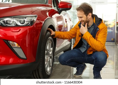 Showroom of modern car dealership. Male customer of car center holding hand on wheel of automobile. Handsome man thinking about characteristics of new red car he want buy.
