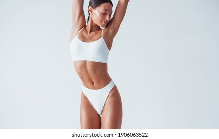 Shows white underwear. Beautiful woman with slim body is in the studio.