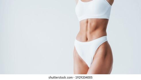 Zeigt weiße Unterwäsche. Schöne Frau mit schlankem Körper ist im Studio.