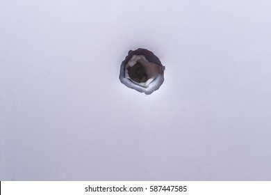Shrapnel hole on the metal fragment from the white surface