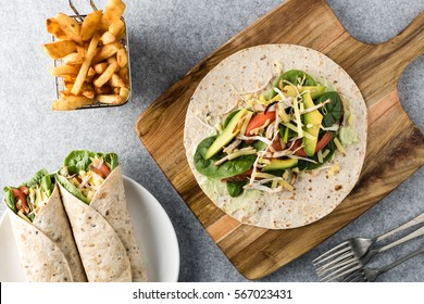 shredded barbecued chicken wraps with carrot, cheese, avocado and spinach. With French fries on the side.