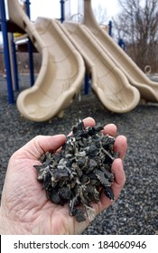 Shredded and cut pieces of used recycled automobile rubber tire crumb reused as soft surface ground floor filler mulch compound on children amusement playground for safety and injury prevention