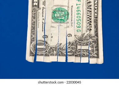 A shredded dollar bill isolated on blue.  The image can be used for economic financial inferences.