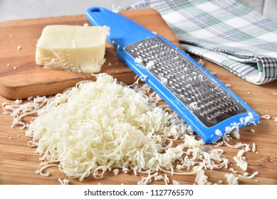 Shredded mozzarella cheese on a cutting board next to a cheese grater