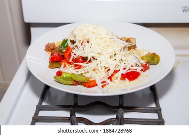Shredded mozzarella cheese on a plate of spaghetti and bell peppers