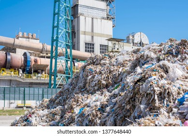Shredded municipal waste used as alternative fuel and rotary cement kiln in the background