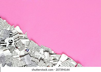 Shredded newspaper pieces in bottom left corner on a dark pink surface.