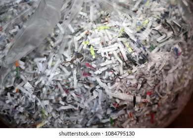 Shredded paper. A clear trash bag of confetti shredded paper and documents.