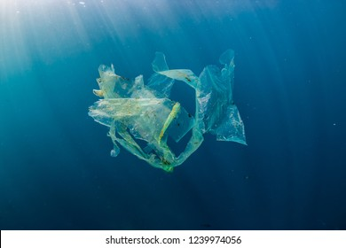 A shredded plastic bag drifting under the surface of a blue, tropical ocean
