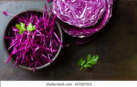 Shredded red cabbage in clay bowl on black background. Vegetarian healthy food. Top view