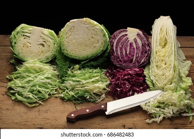 Shredded  white, red,  Savoy and chinese cabbage on a cutting board