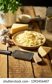 Shredded yellow cheese with cheese grater and capers and basil on old kitchen table