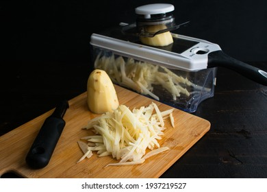 Shredding Potatoes with a Mandoline: Using a mandoline to julienne russet potatoes - Shutterstock ID 1937219527