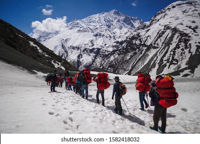 Shree Karka, Nepal - April 25,2019: Hikers are seen walking at Tilicho Base Camp in Annapurna Circuit (Focus on mountain)