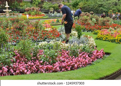 Shrewsbury, Shropshire, UK - August 3rd 2018: Gardeners work at trimming the lawns in the famous dingle gardens in the center of the quarry park in Shrewsbury.