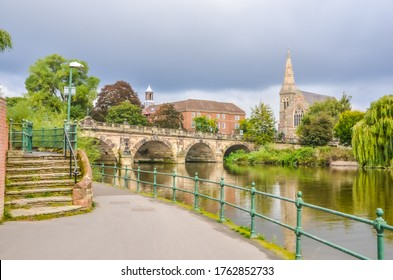 Shrewsbury town river scene with bridge and church. No people, green trees.