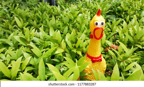 Shrilling chicken squeaky toy. Toy rubber shriek yellow chicken on tree background. Fun with nature concept.