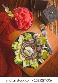 Shrimp aguachile in a stone molcajete accompanied by strawberry margarita