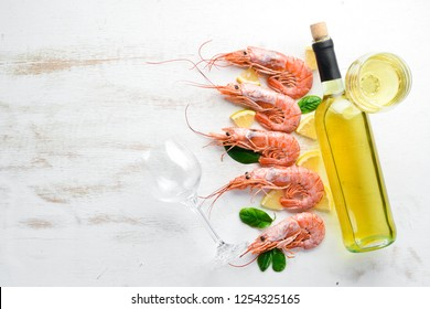Shrimp with a bottle of white wine. Top view. Free space for your text. On the old background.