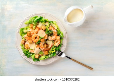 Shrimp Caesar salad with Parmesan cheese, croutons and lettuce, with a fork and the sauce in a gravy boat, shot from the top with a place for text