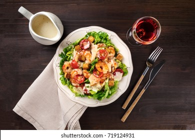 Shrimp Caesar salad with Parmesan cheese, croutons, lettuce, and cherry tomatoes, with a fork, knife, sauce in a jar, and a glass of rose wine, shot from above on a dark rustic background texture